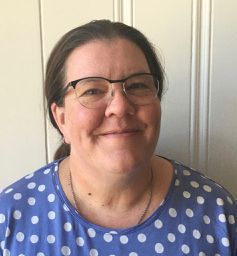 Woman in a blue and white polka dot shirt with glasses on face, smiles at the camera