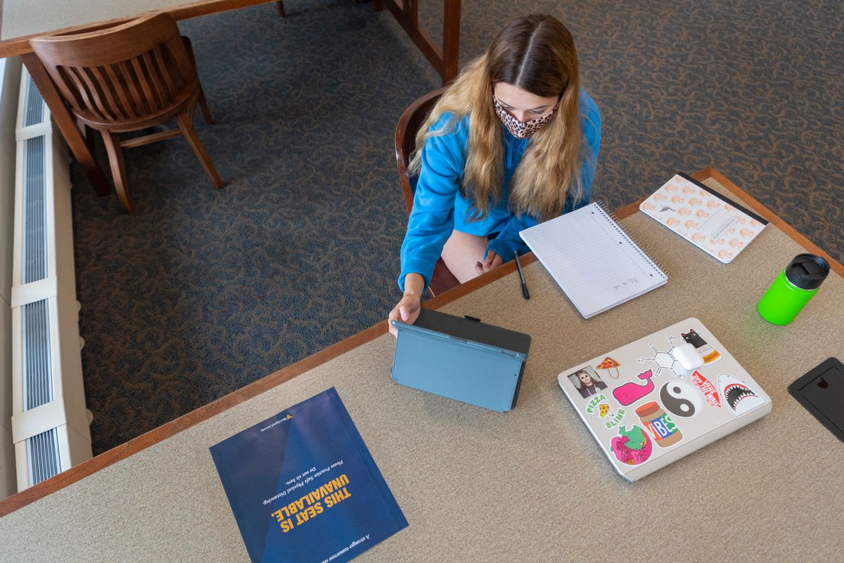 woman sits at table with folders, papers
