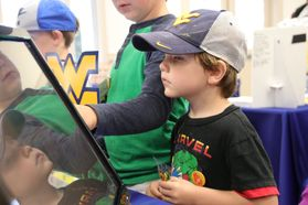 Young boy in a black t-shirt and wv hat plays a digital game while staring at a screen.