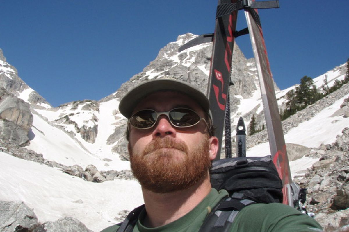 Man with red hair and beard, wearing sunglasses and a hat on a mountain