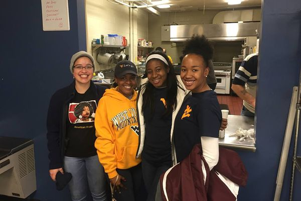 Four young women stand in a doorway; all are wearing WVU gear