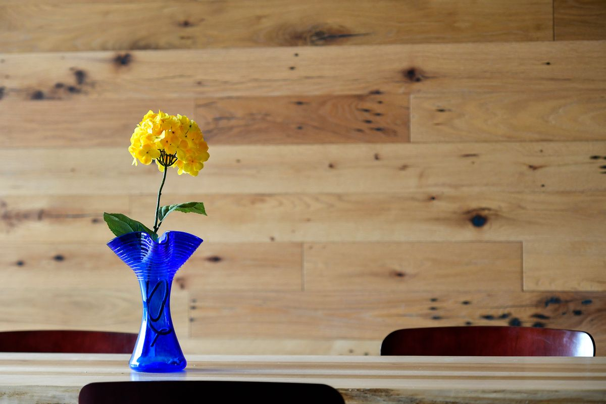 Yellow flower in blue vase sitting on table
