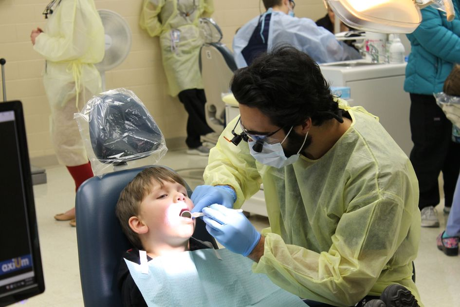 Dentist works on child.