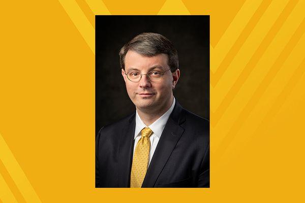 photo of stern-looking man in dark suit, gold tie, glasses