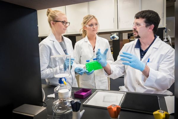 Travis Knuckles, assistant professor in the WVU School of Public Health, works with undergraduate research assistants (L to R) Allison Tolbert, a public-health major, and Haley Twilley, a recent graduate of the public-health program.