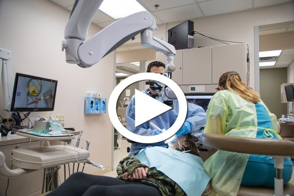 dentist, assistant examine a patient using a camera. Large white triangle in a circle super-imposed over photo