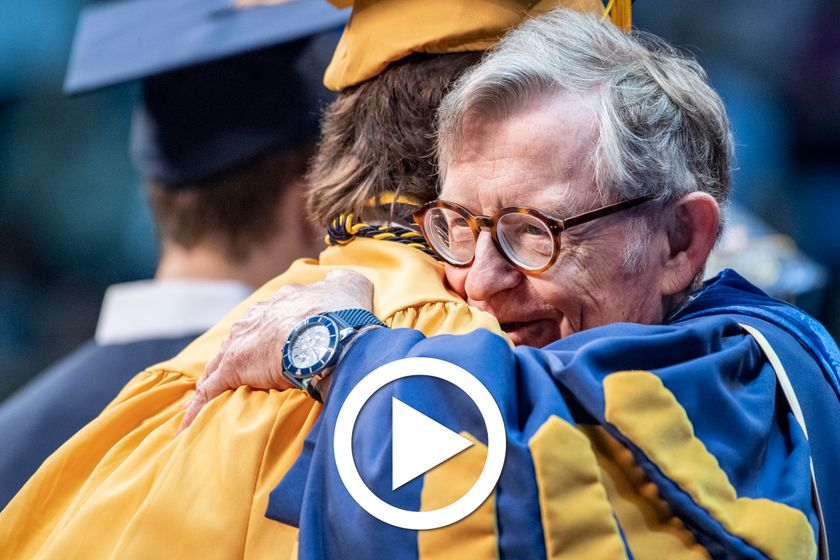 man hugs a college graduate as he receives his degree
