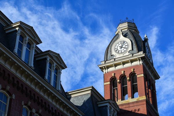 clock tower against blue sky with feathery clouds