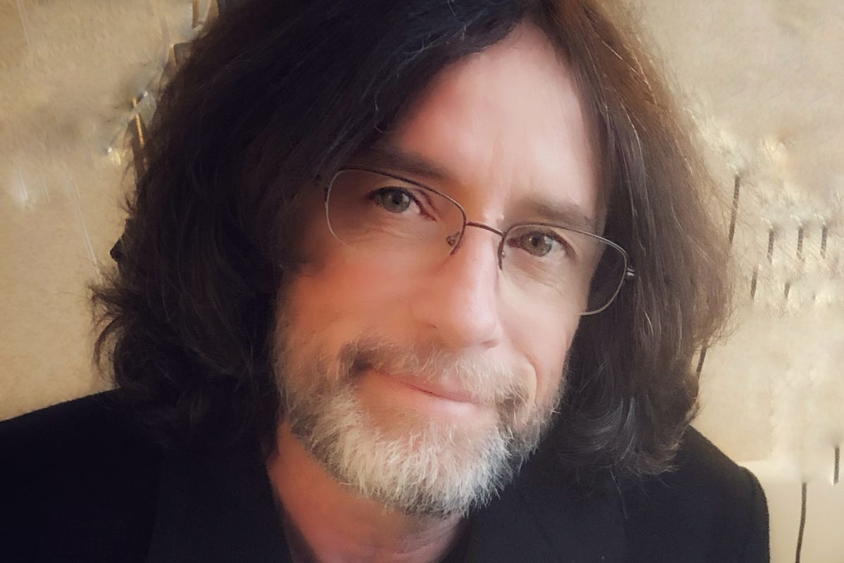 man with long brown hair and glasses smiles