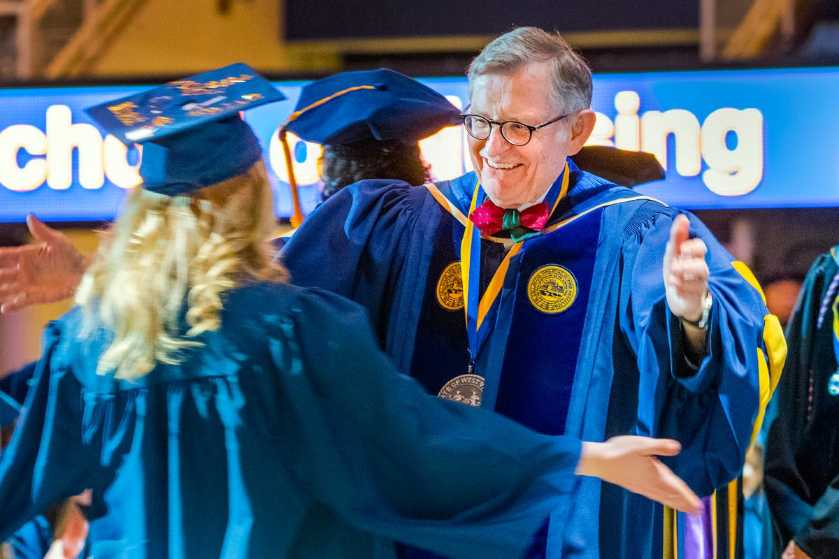 man with grey hair and glasses in a graduation gown greets female student in cap and gown on stage
