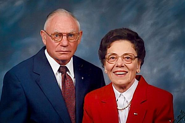 portrait of a man in a blue suit with a red tie, and a woman in a red suit and white blouse