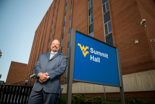 Bill Bayless stands beside WVU's Summit Hall sign