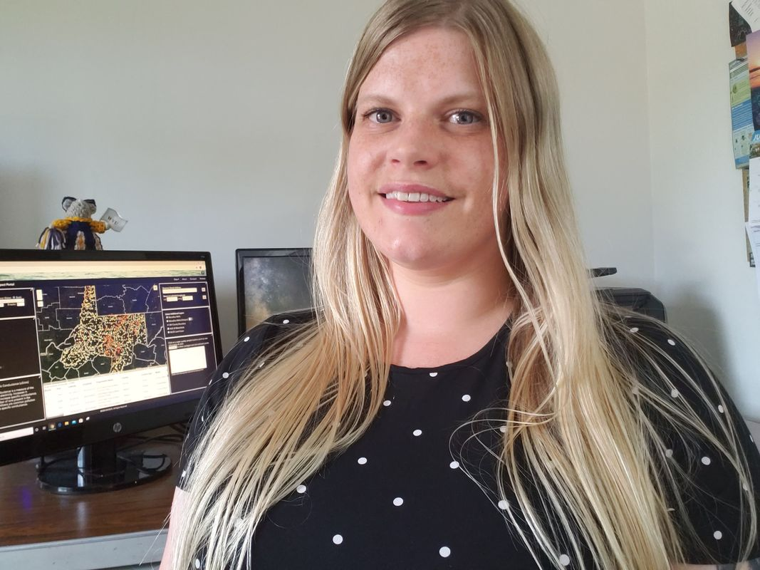 smiling white woman in front of computer