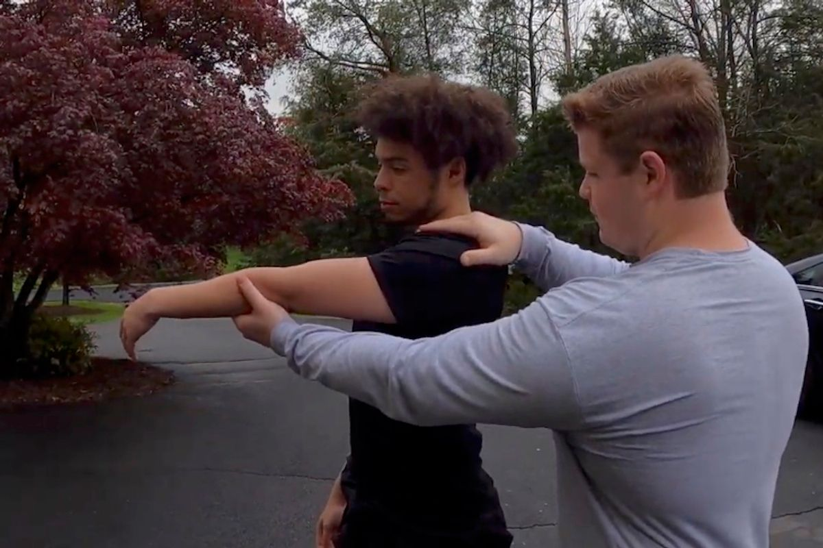 Two men stretching one man's arm