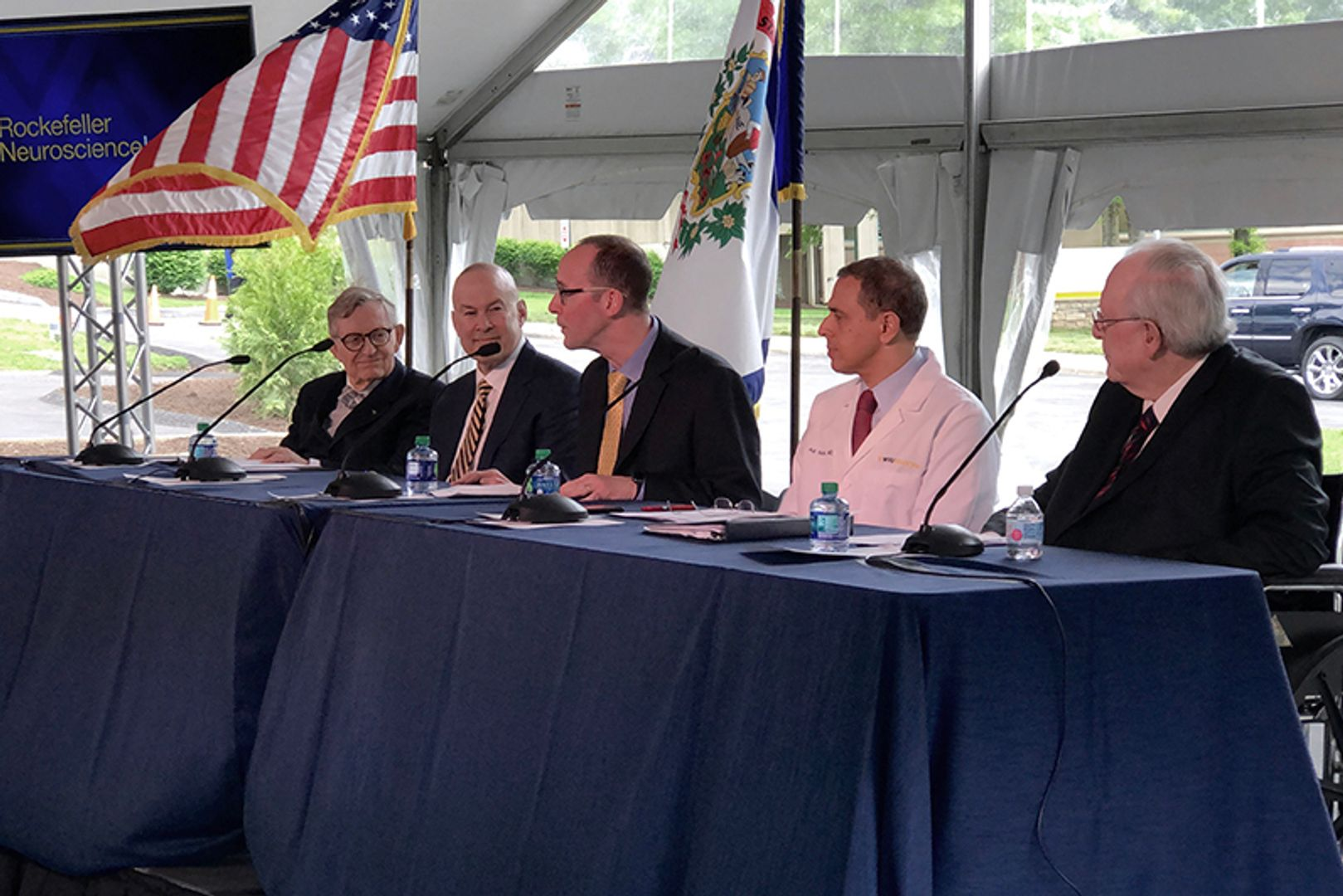 five men sitting behind microphones at a table draped in dark blue cloth