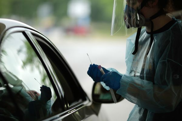 person in PPE at a car window
