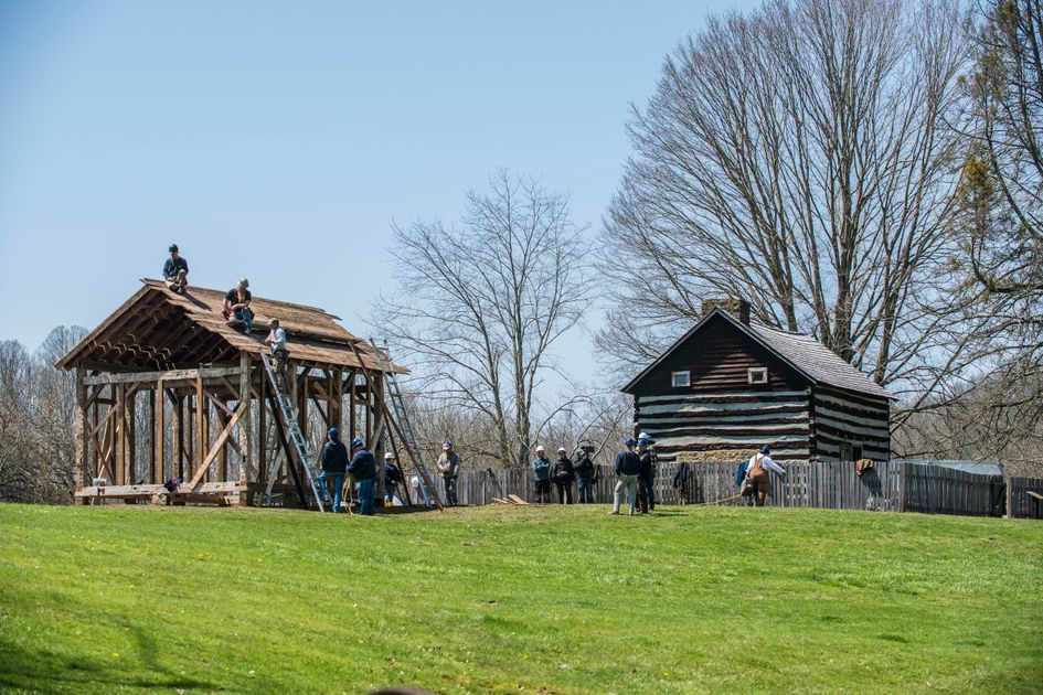 Photo of workers working on two barns surrounded by grass and trees.