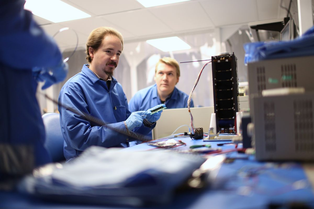 Men dressed in blue work in a lab