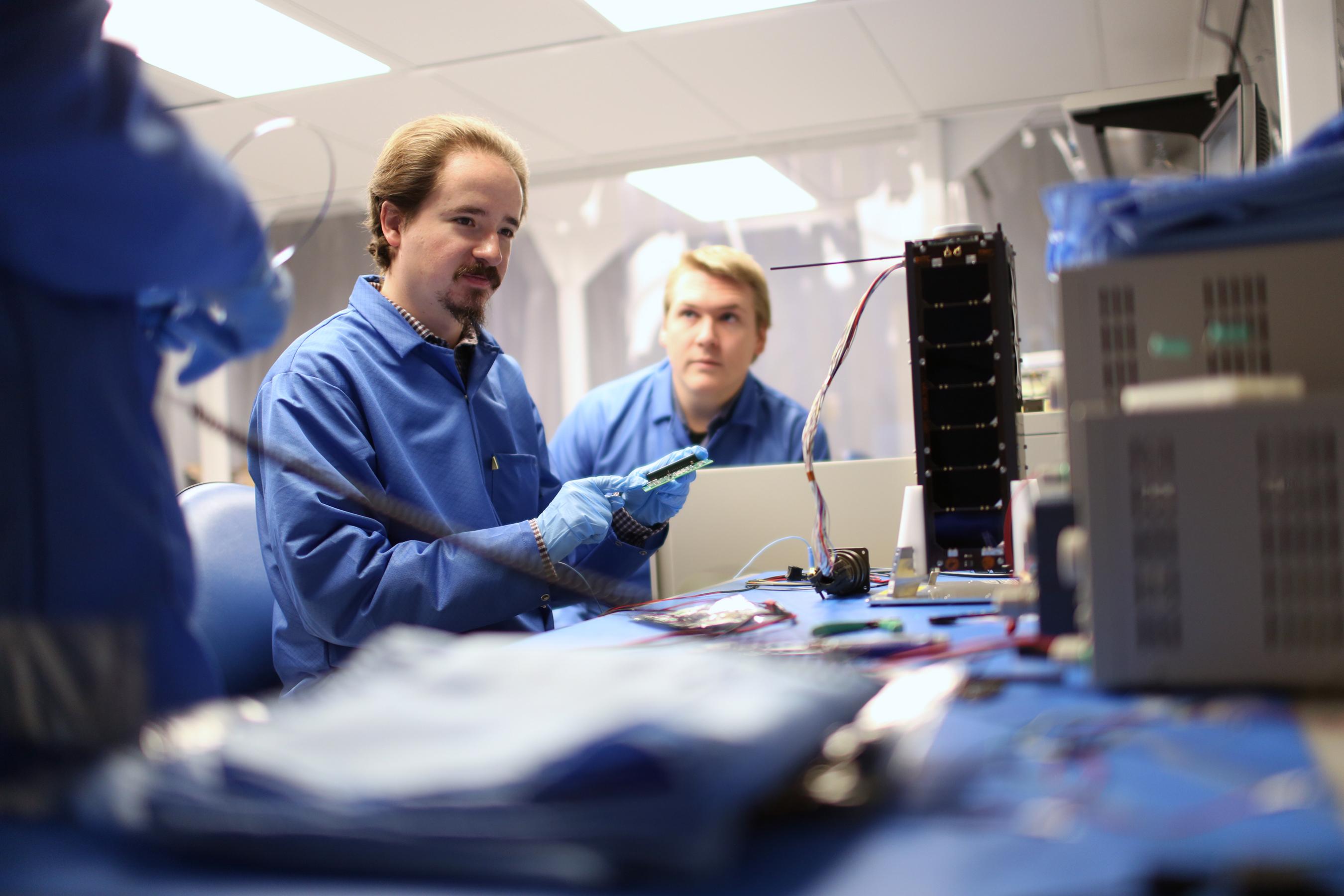Men dressed in blue work in a lab