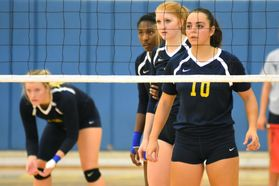 Volleyball players prepare to receive serve
