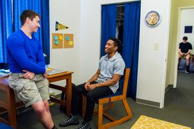 Two male students hang out in University Hall room