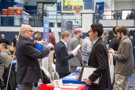 Students talk with potential employer at career fair