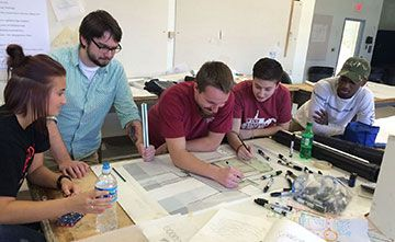 Five Students Working On Design Drawing