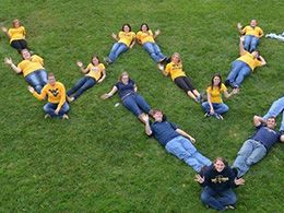 Students forming WV in by laying in the grass