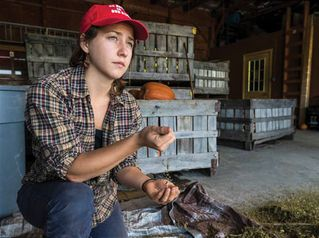 Student in a barn with produce