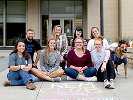 REM student group posing in front of building with REM Club written on sidewalk in front of them