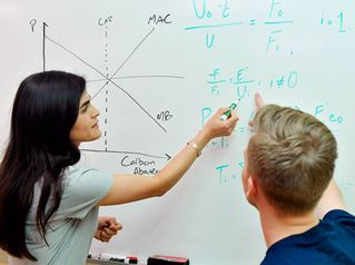Two students working on a white board