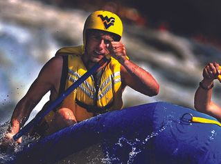 Student with WVU helmet whitewater rafting