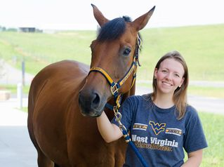 Student in WVU t-shirt standing next to a horse