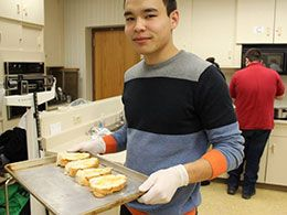 Student holding a tray of baked goods