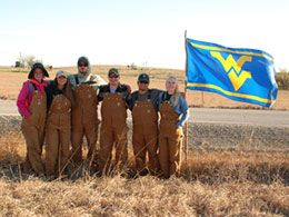 Students in coveralls with WVU flag