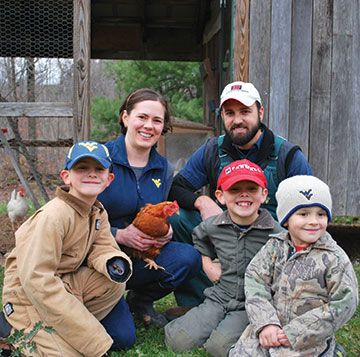 The Kenny family holding a chicken