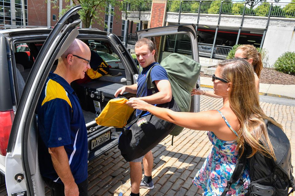Student and family packing into car to move in.