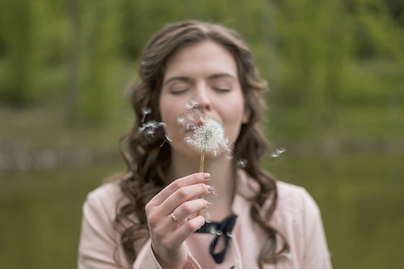 A woman blows dandelion seeds into the air