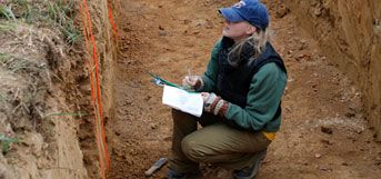 image of student in pit examining soil