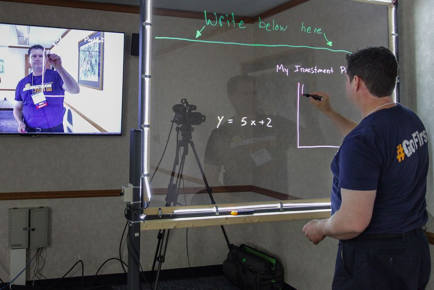 Person drawing on glass with neon markers while being video recorded.