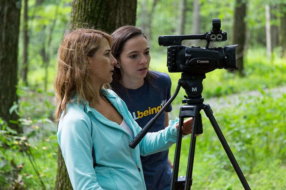Julie Black and Eva Buchman profile looking into a Canon camera pointed off scene with a green wooded background.