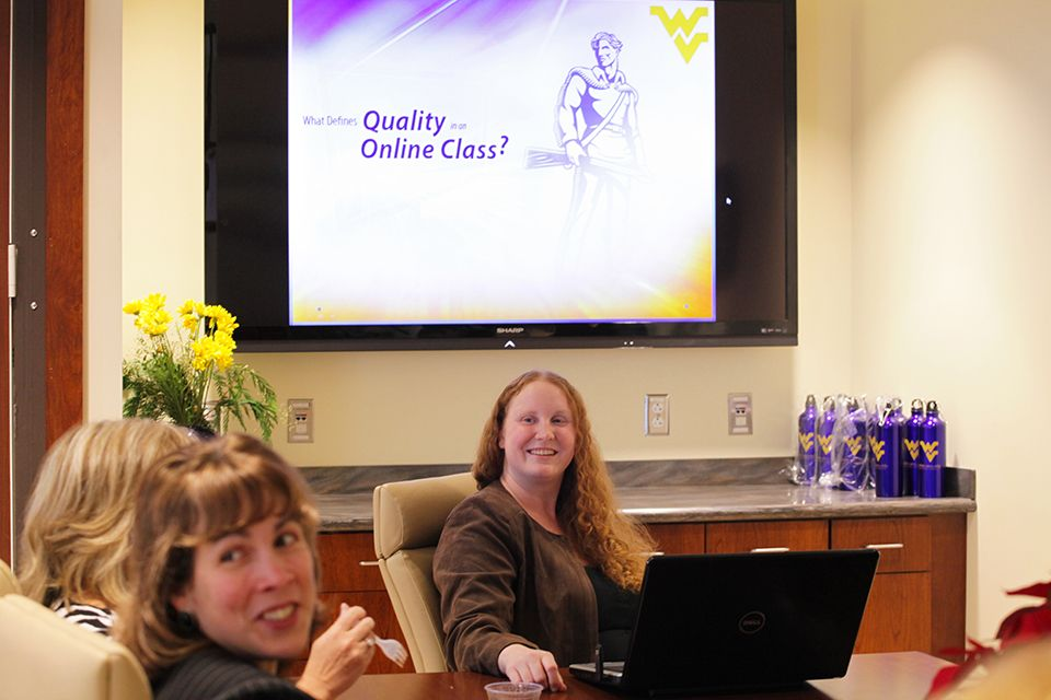 Tracey Beckley and Erin Kelley face the camera, in front of a screen with 'What Defines Quality in an Online Class?' displayed on it.