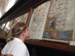 Students looks at illuminated manuscript under glass