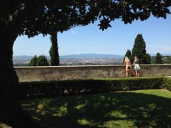 two students look over a wall in garden