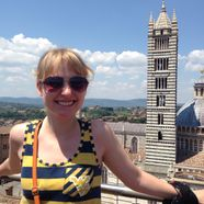smiling young woman stands in front of cathedral of siena