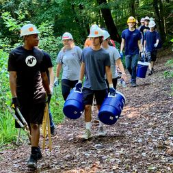 Volunteers along trail carrying water jugs and tools