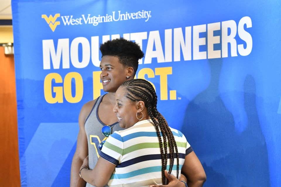 A mother and son pose in front of a Mountaineers Go First banner