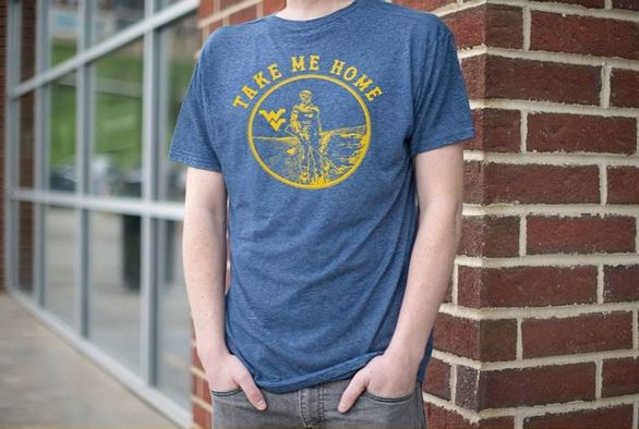 "Student wearing the winning shirt. The winning shirt is blue with a gold emblem on the front containing the Mountaineer and the Flying WV. Around the emblem are the words ""Take Me Home""."