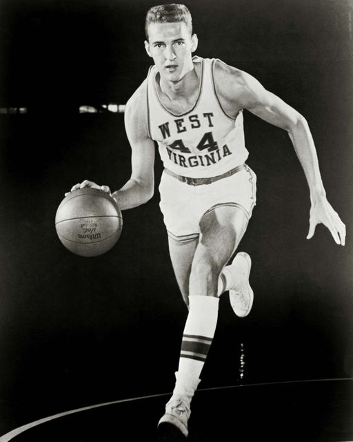 A posed, black-and-white photo of Jerry West dribbling a basketball