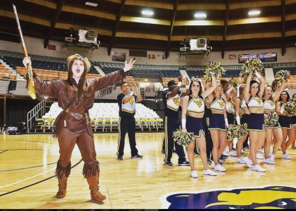 Mountaineer mascot and cheerleaders on a basketball court